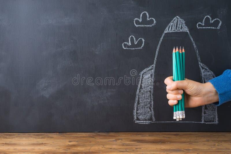 Tillbaka till skolabegreppet med handen som rymmer blyertspennor över svart tavlaraket, skissa bakgrund royaltyfria bilder