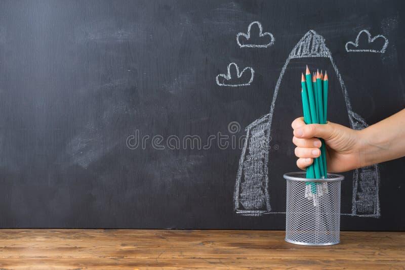 Tillbaka till skolabegreppet med handen som rymmer blyertspennor över svart tavlaraket, skissa bakgrund arkivbild