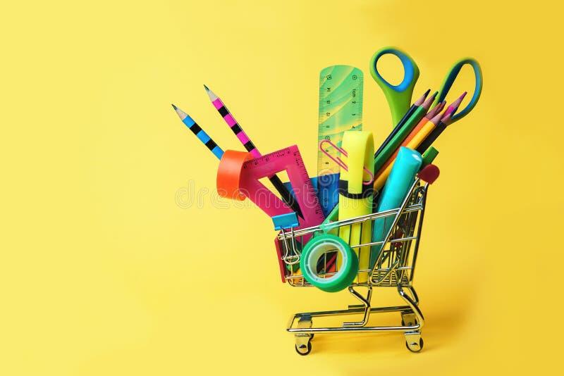 Tillbaka till skolabegreppet med shoppingvagnen och färgrika blyertspennor, fyrkantig linjal, sax, gem, markörer på den pastellfä fotografering för bildbyråer