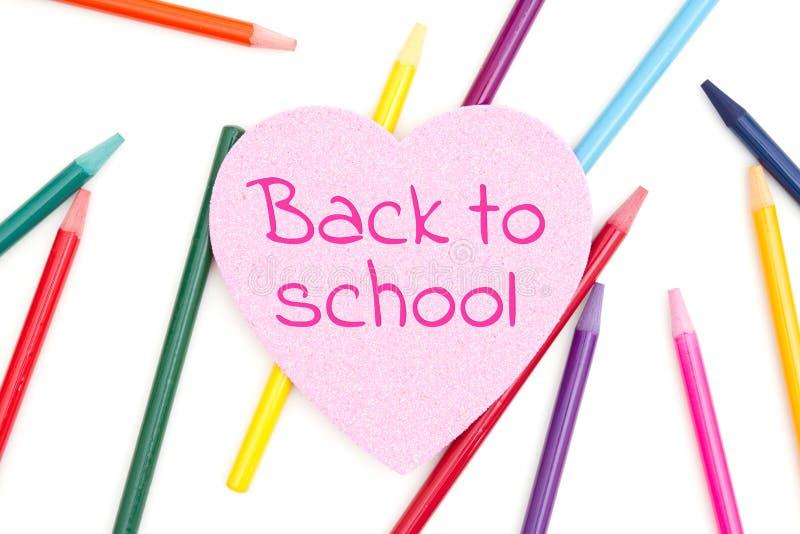 Tillbaka till skolameddelandet på rosa blänka hjärta med kulöra vattenfärgblyertspennor arkivfoto