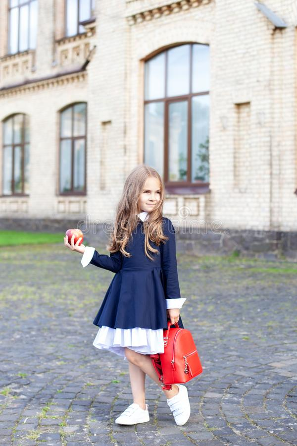 Tillbaka till skolan En liten flicka i förskoleåldern står med en ryggsäck och ett äpple på sin första dag i skolan eller på dagh arkivfoton