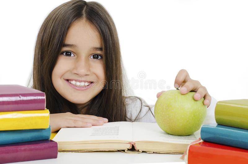Tillbaka till skolan och lycklig tid! Cute, ett flitigt barn sitter vid ett skrivbord Flickan läser boken royaltyfri fotografi