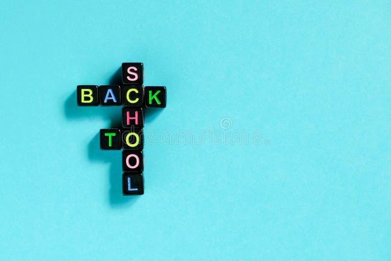 Tillbaka till skolatext från färgrika bokstäver på svarta kuber som läggas ut i form av korsordpusslet, blå bakgrund Begreppsutbi royaltyfri foto