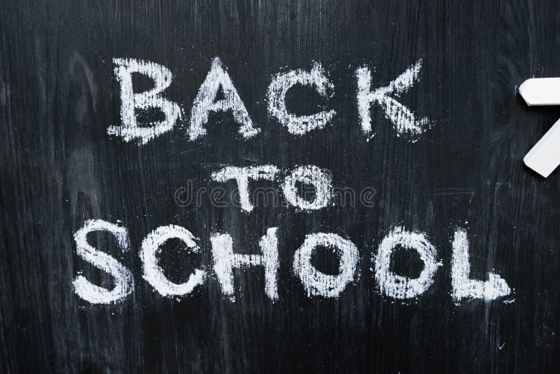 Tillbaka till skolauttrycket som är skriftligt på en svart träbakgrund, bästa sikt royaltyfria foton