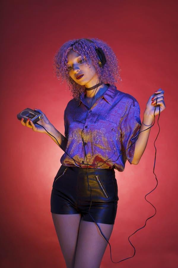 Tillbakablick av en ung kvinna som lyssnar till musik med hennes walkman arkivbild