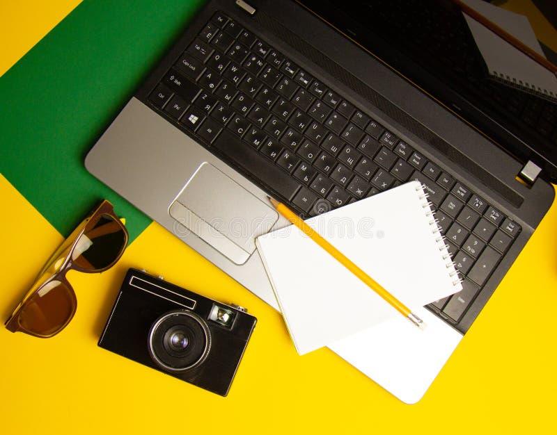 Tillbehör för arbete med lopp på stranden: bärbar dator anteckningsbok, telefon, tappningkamera, penna, solglasögon på en gul bak royaltyfria foton