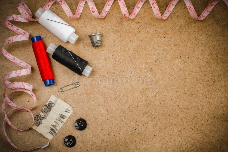 Tillbehör för att sy: visare, trådar, knappar, en fingerborg, ett stift och en måttband royaltyfri foto