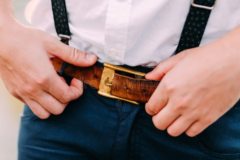 Tillbehör för man` s Hipster som sätter på ett brunt läderbälte Mannen räcker närbild klädbegrepp arkivfoton