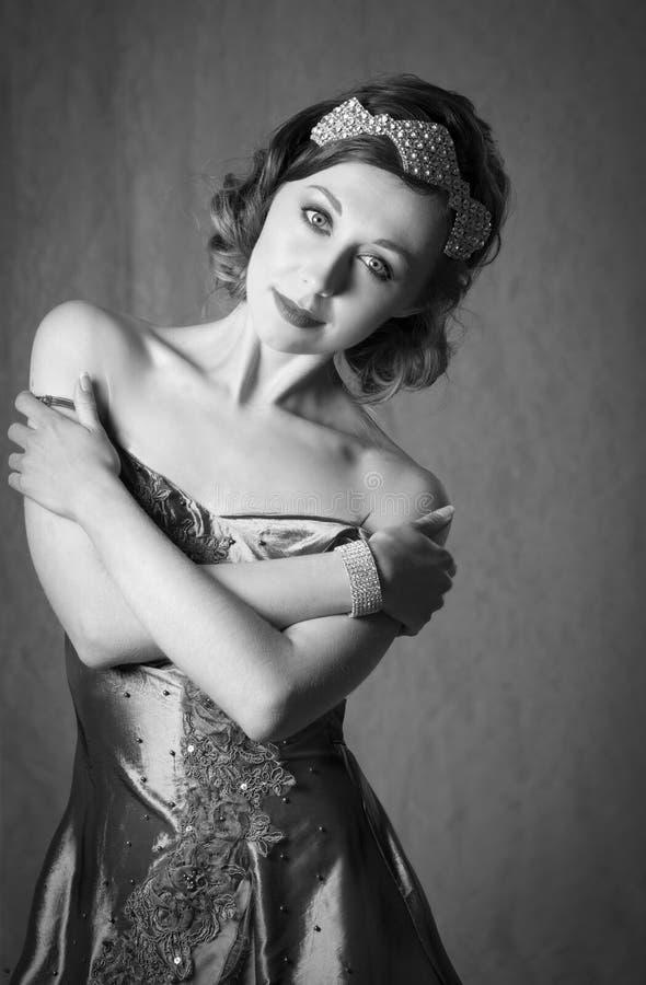 Tillbehör och armband för hår för diamant för älskvärd tjugotalkvinna som bärande poserar i en grå aftonklänning för tappning royaltyfria foton