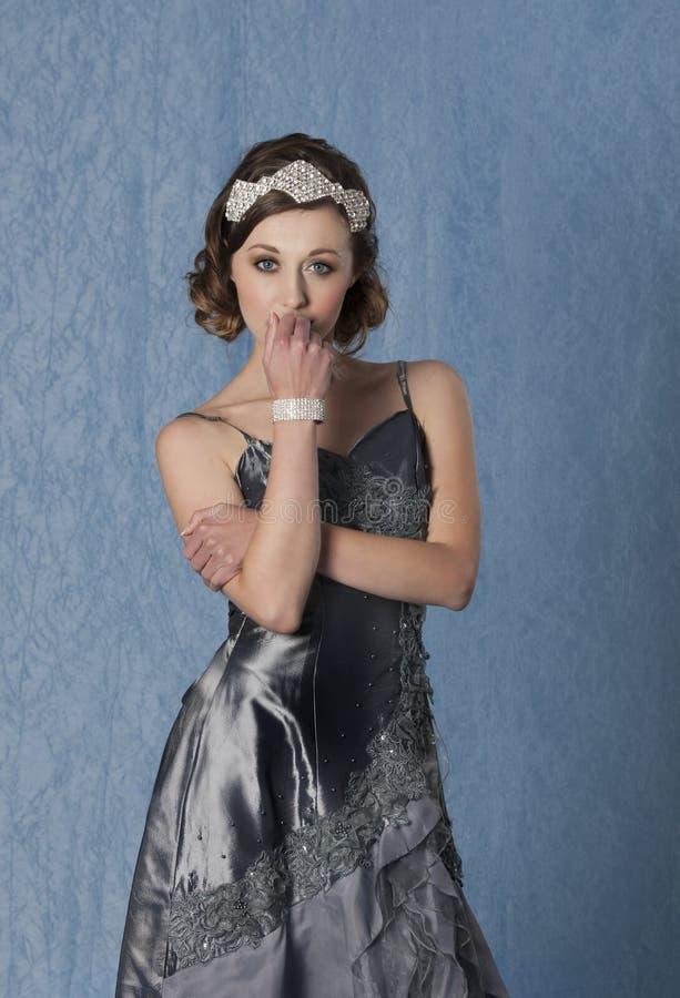 Tillbehör och armband för hår för diamant för sexig tjugotalkvinna som bärande framme poserar av en blå bakgrund i en grå aftonkl arkivbild