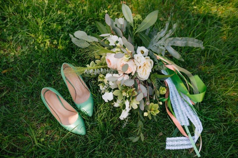 Tillbehörbrudbuketten skor grönt gräs royaltyfri bild