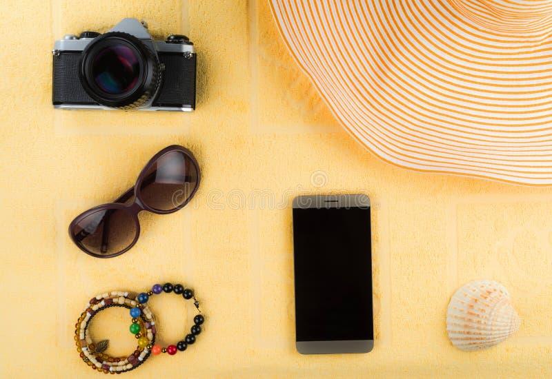 Tillbehören för kvinna` s för en strand semestrar En smartphone med en tom skärm, en randig hatt, smycken, solexponeringsglas, fi royaltyfri bild