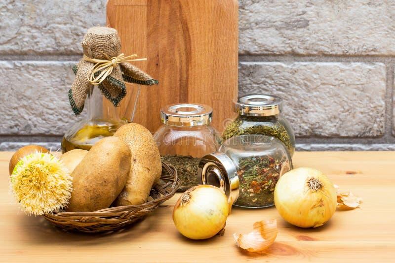 Tillbringare av olivolja, potatisar, lök, skärbräda och kryddor i krusen royaltyfria bilder