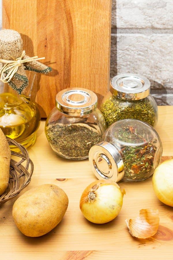 Tillbringare av olivolja, potatisar, lök, skärbräda och kryddor i krusen arkivbild
