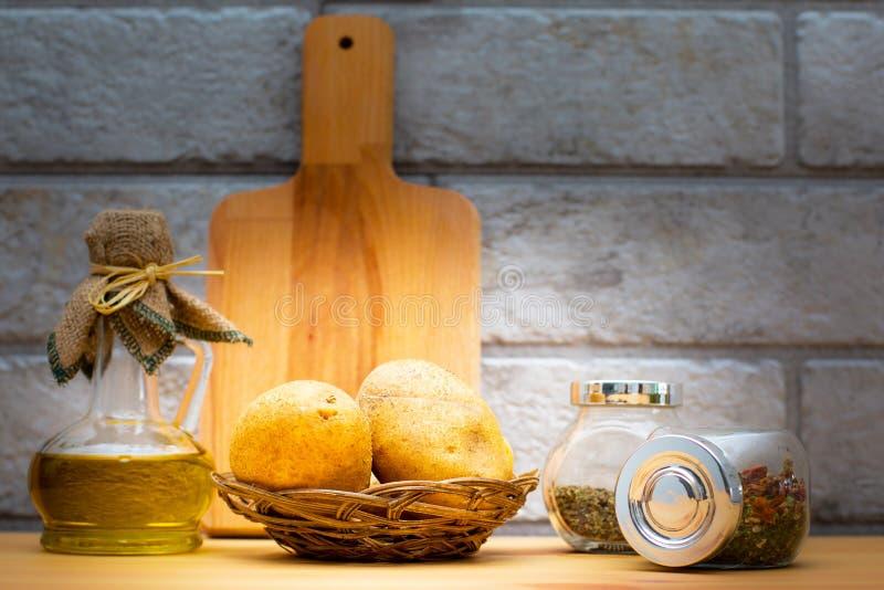 Tillbringare av olivolja, potatisar, skärbräda och kryddor i krusen arkivbild