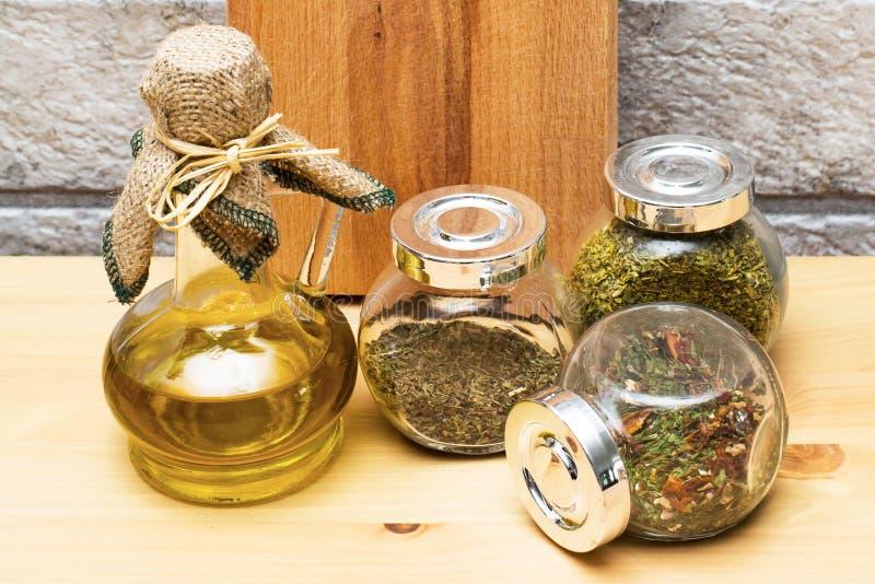 Tillbringare av olivolja, skärbräda och kryddor i krusen fotografering för bildbyråer