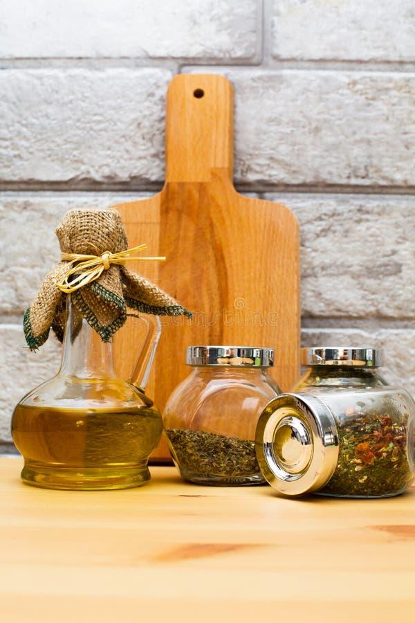 Tillbringare av olivolja, skärbräda och kryddor i krusen royaltyfri foto