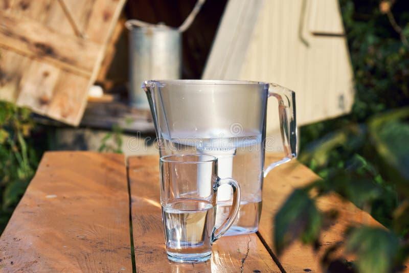 Tillbringare för vattenfilter och en genomskinlig kopp av vatten med en by väl på bakgrunden royaltyfri fotografi