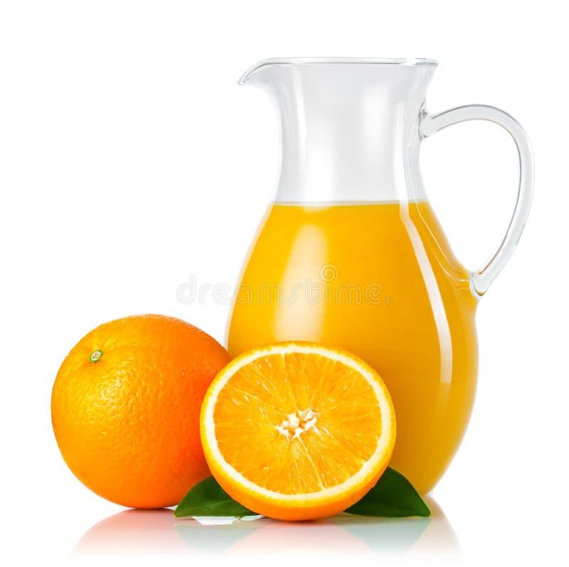 Tillbringare med orange fruktsaft och frukter med gröna sidor som isoleras på w royaltyfria foton