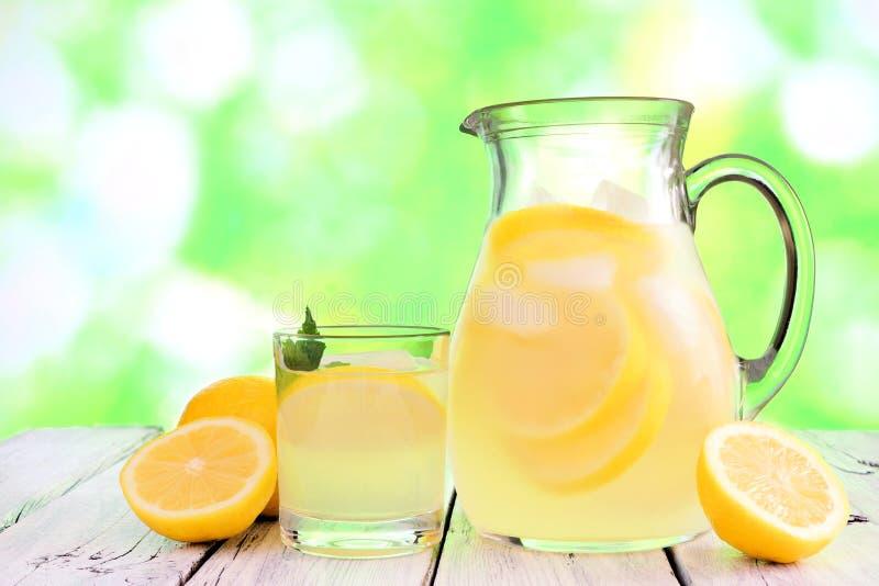 Tillbringare och exponeringsglas av lemonad mot grön det friabakgrund fotografering för bildbyråer