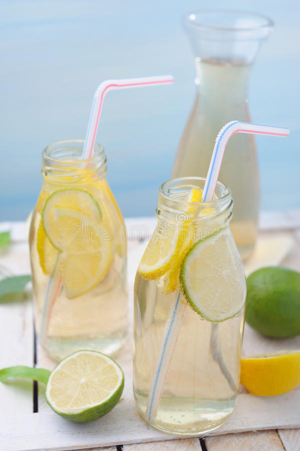 Tillbringare och exponeringsglas med lemonad, citroner och limefrukt på den lantliga tabellen royaltyfria bilder