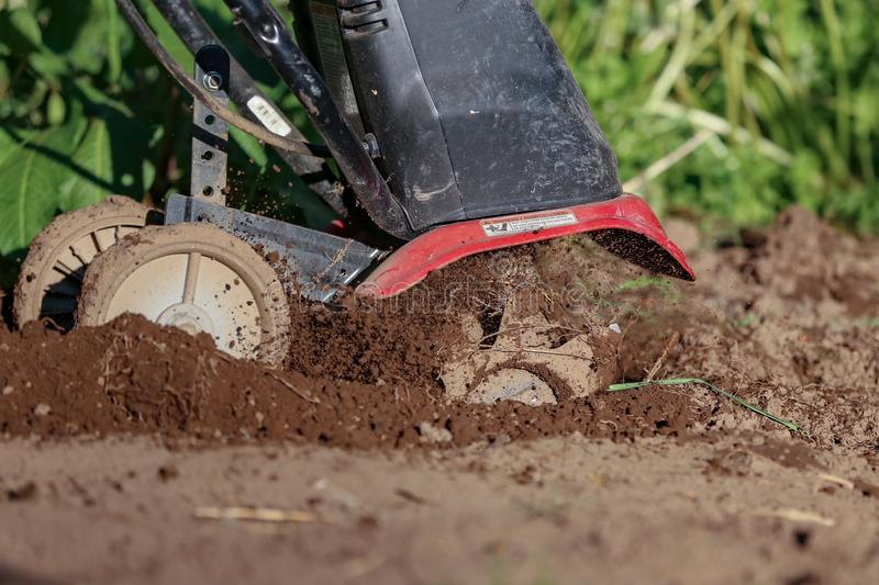 Tiller in action digging and spewing dirt. And soil in the garden stock photography