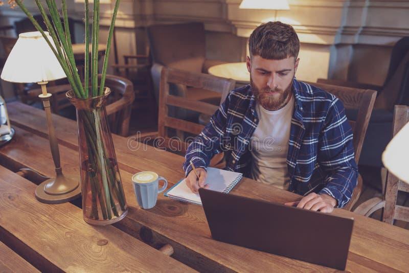 Tillfällig affärsman eller freelancer som planerar hans arbete på anteckningsboken, arkivfoto