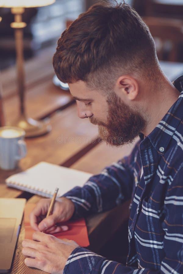 Tillfällig affärsman eller freelancer som planerar hans arbete på anteckningsboken, royaltyfri bild