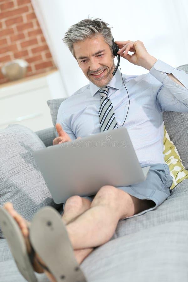 Tillfällig affärsman med bärbara datorn som arbetar på soffan royaltyfri fotografi