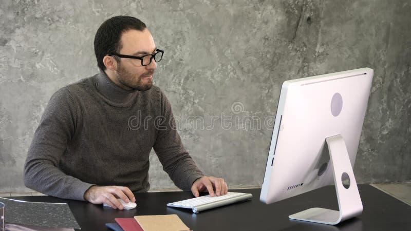 Tillfällig affärsman som i regeringsställning fungerar och att sitta på skrivbordet och att skriva på tangentbordet som ser dator arkivfoto