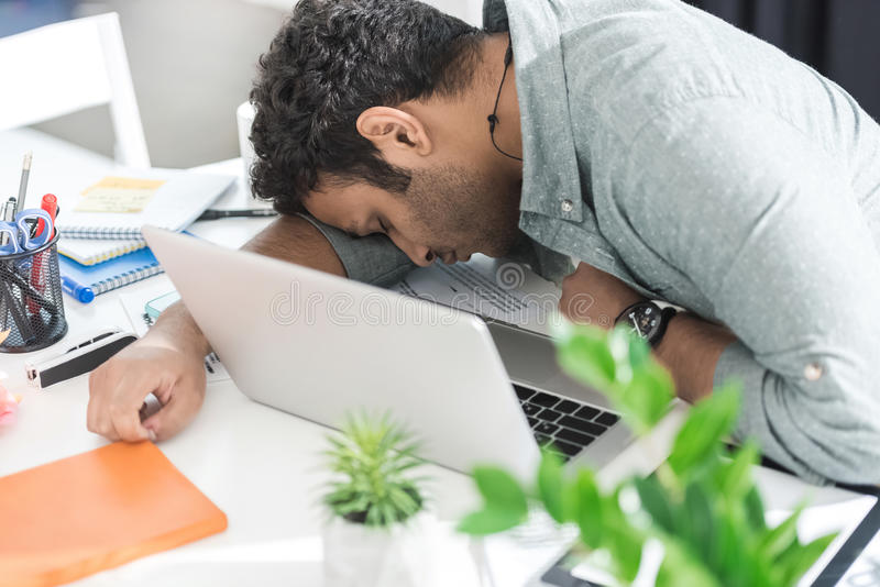 Tillfällig affärsman som sover på tabellen nära bärbara datorn på det moderna kontoret arkivbilder