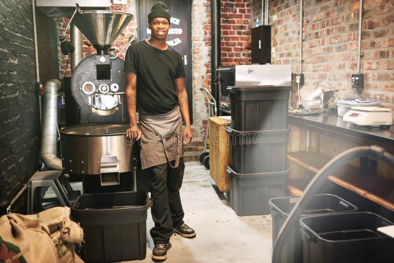Tillfällig arbetaranseende och benägenhet mot en kaffebrännare för kaffeböna royaltyfri bild