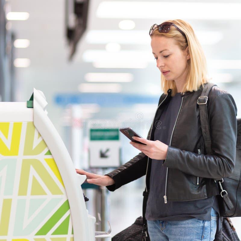 Tillfällig caucasian kvinna som använder den smarta telefonapplikation- och incheckningmaskinen på flygplatsen som får logipasser royaltyfri bild