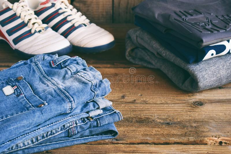 Tillfällig dräkt för tonåring Pojkeskor, kläder och tillbehör på träbakgrund - tröja, skjorta, byxa, jeans, gymnastikskor arkivbild