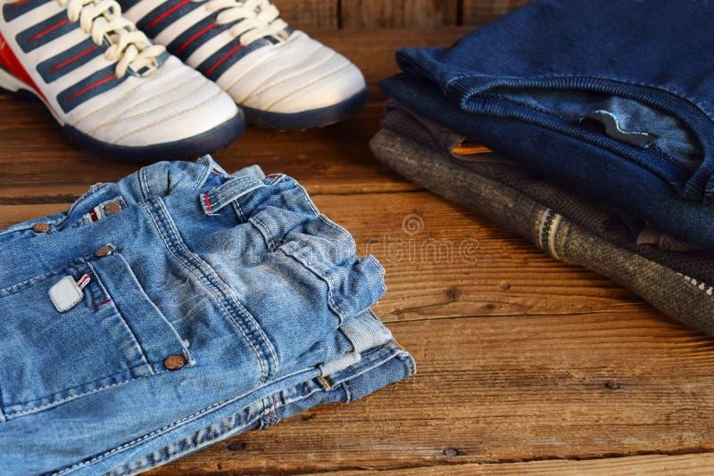 Tillfällig dräkt för tonåring Pojkeskor, kläder och tillbehör på träbakgrund - tröja, skjorta, byxa, jeans, gymnastikskor överkan arkivbilder