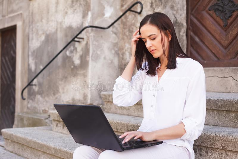 Tillfällig härlig ung kvinna som arbetar på en bärbar dator royaltyfri foto