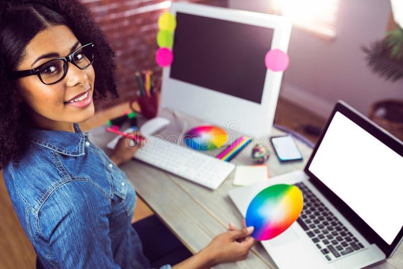 Tillfällig kvinnlig formgivare som ler och rymmer färgdiagrammet arkivbild