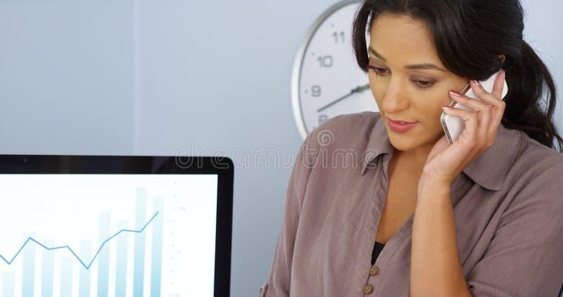 Tillfällig latinamerikansk affärskvinna som i regeringsställning talar på mobiltelefonen arkivbilder