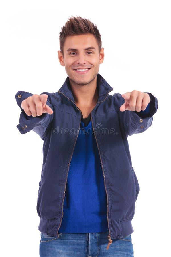 Tillfällig man i omslag som pekar hans fingrar till kameran fotografering för bildbyråer