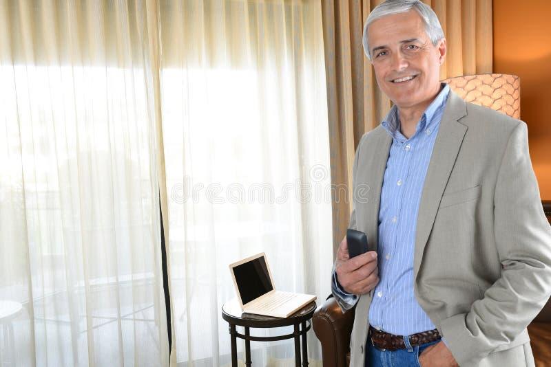 Tillfällig mogen affärsman i hans hotellrum arkivbilder