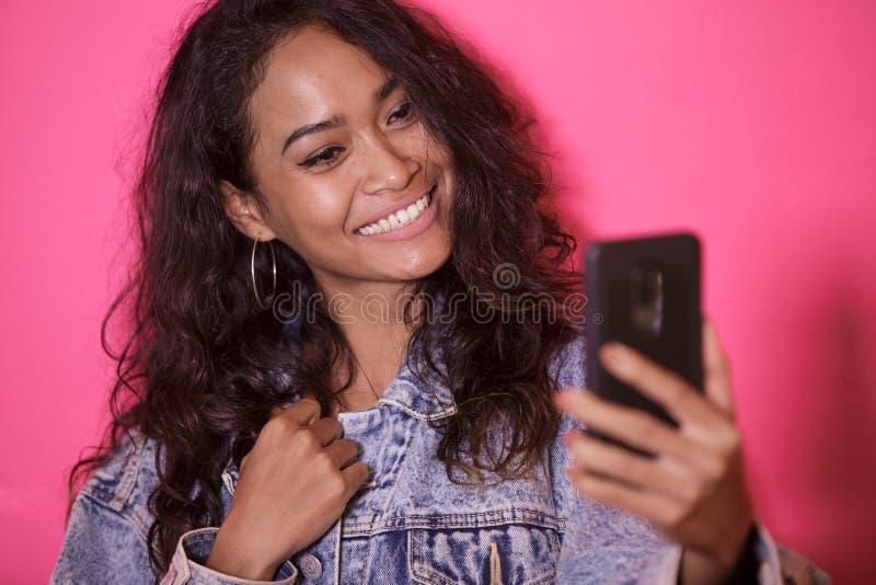 Tillfällig nätt kvinna som tar selfies genom att använda mobiltelefonkameran fotografering för bildbyråer