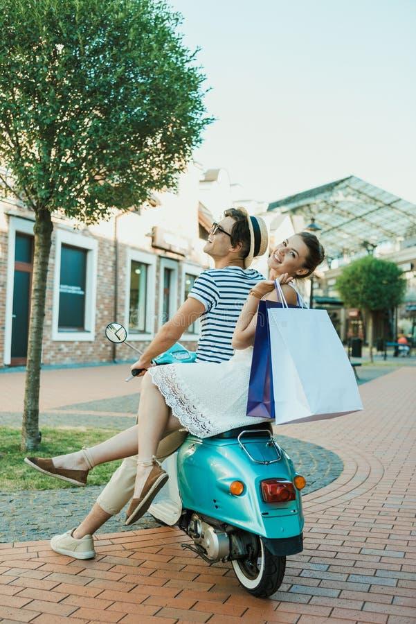 Tillfällig parridning på var nedstämd och rymmande shoppingpåsar utomhus arkivfoton