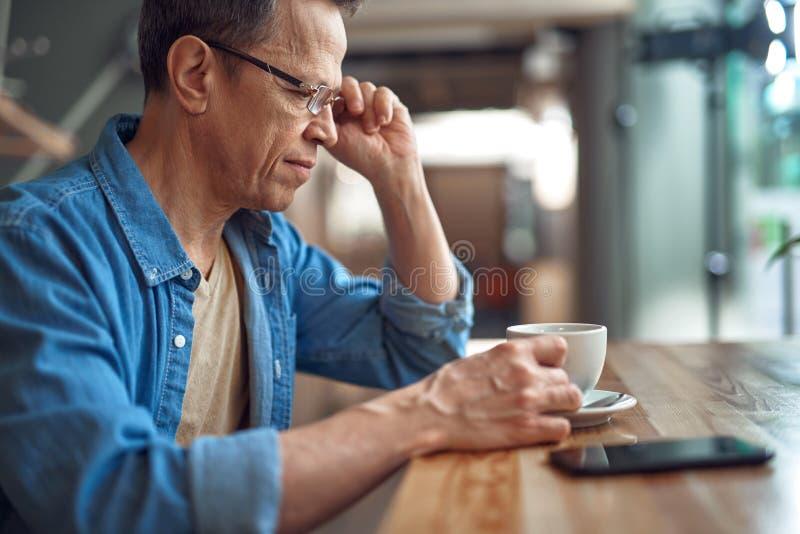 Tillfällig stil åldrades mannen som sitter i kafé med kaffe arkivbilder