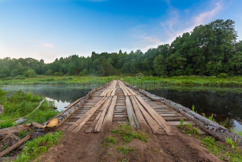 Tillfällig träbro över floden för tunga lastbilar, lastbilar, bilar och medel för vagnsträ under deforestatio royaltyfri bild