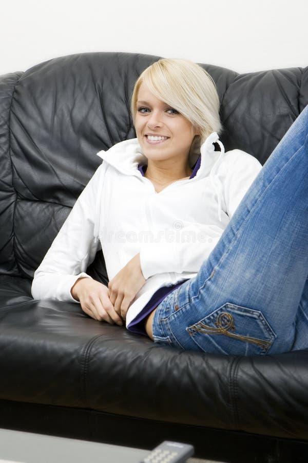 Tillfällig ung kvinna som kopplar av på en lädersoffa fotografering för bildbyråer