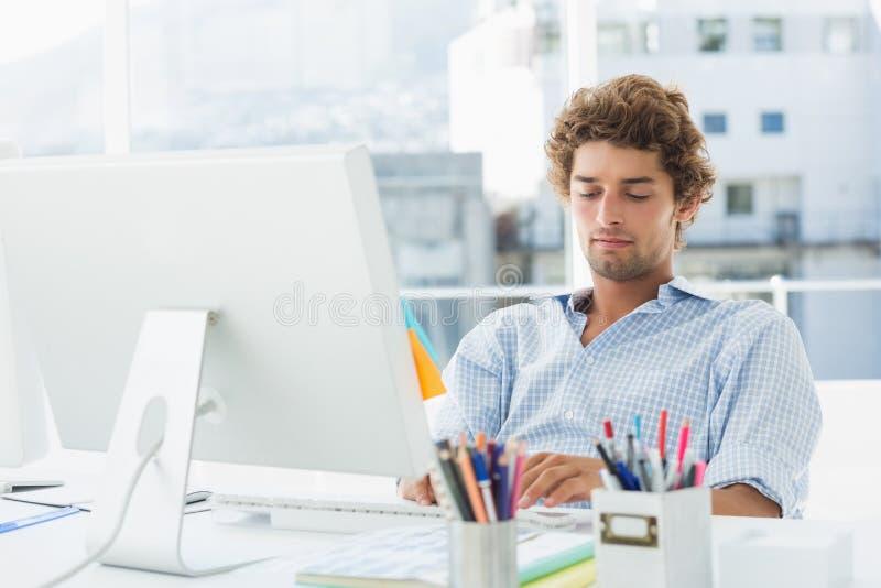 Tillfällig ung man som använder datoren i ljust kontor royaltyfri fotografi