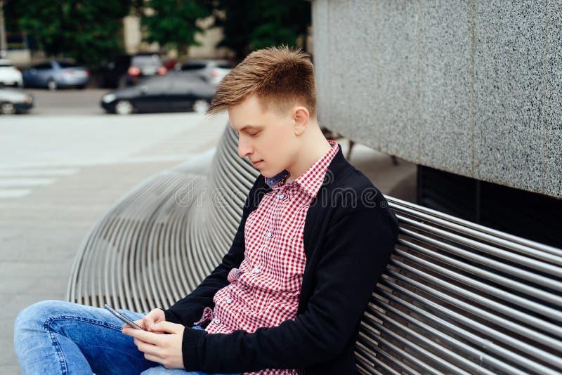Tillfällig ung man som använder den smarta telefonen som sitter på bänk i stad arkivbild