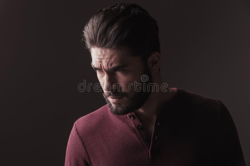 Tillfällig ung man som ser ilsken i väg från kameran royaltyfri bild