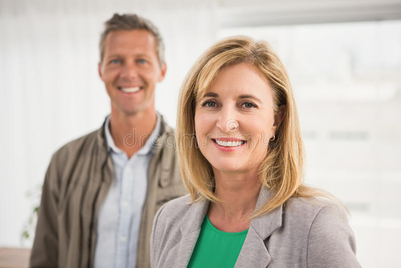 Tillfälliga affärskollegor som ler på kameran royaltyfri fotografi
