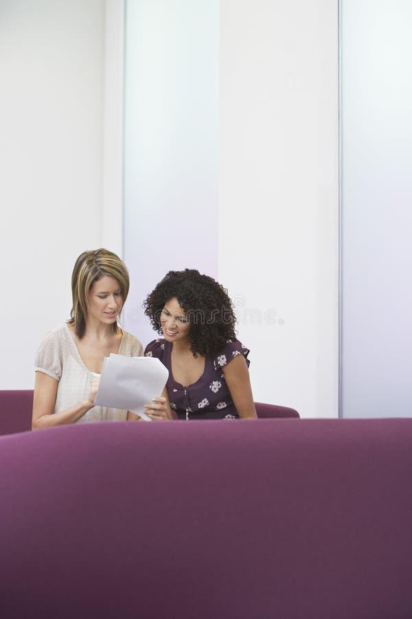 Tillfälliga affärskvinnor som går över dokument på soffan arkivbild